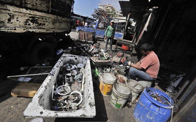 Un homme démonte et trie des appareils éléctriques dans un atelier du quartier de Bab al-Tabbané à Tripoli, dans le nord du Liban, le 3 juin 2020. (Crédit : JOSEPH EID / AFP)