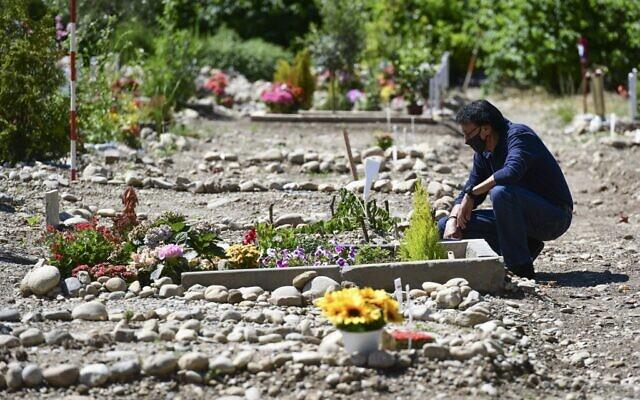 Le Marocain Mustapha Moulay, qui vit en Italie depuis 32 ans, prie à côté de la tombe de sa femme, décédée le 7 avril 2020 du COVID-19, le 5 juin 2020, dans la section musulmane d'un cimetière majoritairement catholique romain de Bruzzano, dans la périphérie de Milan. (Crédit : Miguel MEDINA / AFP)