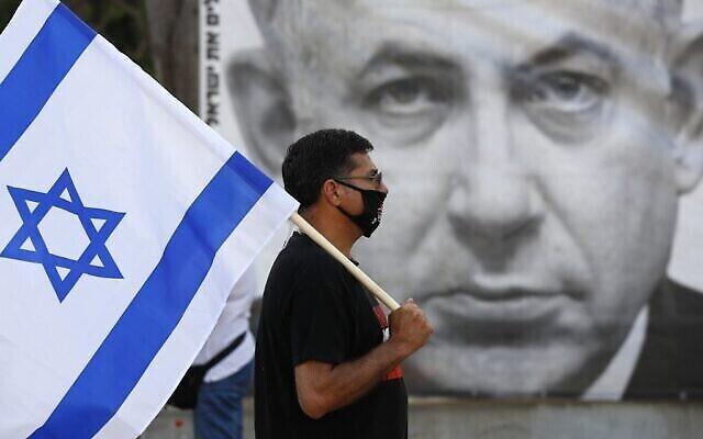 Un manifestant avec le drapeau israélien pendant une manifestation pour dénoncer le projet d'annexion de la Cisjordanie, place Rabin à Tel Aviv, le 6 juin 2020 (Crédit : JACK GUEZ / AFP)