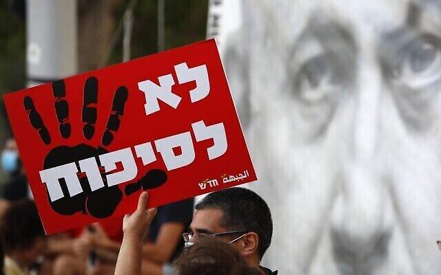 """Un manifestant brandit un panneau sur lequel est écrit """"Non à l'annexion"""" pour dénoncer le projet israélien d'annexion de la Cisjordanie sur la place Rabin de Tel Aviv, le 6 juin 2020 (Crédit : JACK GUEZ / AFP)"""