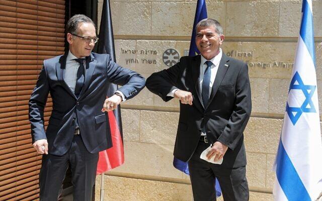"""Le ministre israélien des Affaires étrangères Gabi Ashkenazi (à droite) salue son homologue allemand Heiko Maas avec un """"coup de coude"""", en raison de la pandémie de coronavirus COVID-19, au ministère à Jérusalem le 10 juin 2020. (Menahem KAHANA / AFP)"""