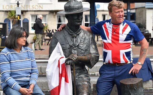 Steve Dorris, un résident local, portant un t-shirt avec le drapeau de l'Union, pose avec une statue de Robert Baden-Powell, le fondateur du mouvement scout, sur le quai de Bournemouth, dans le sud de l'Angleterre, le 11 juin 2020, après le conseil a annoncé qu'il retirerait la statue. (Crédit : Glyn KIRK / AFP)