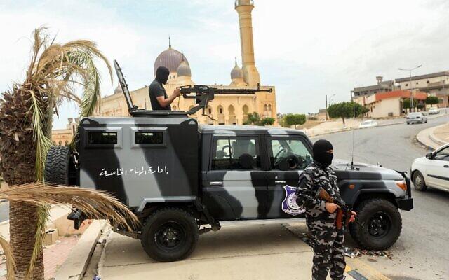 Des membres des forces de sécurité affiliées au ministère de l'Intérieur du gouvernement libyen d'accord national (GNA) se tiennent à un poste de contrôle de fortune dans la ville de Tarhuna, à environ 65 kilomètres au sud-est de la capitale Tripoli, le 11 juin 2020. (Crédit : Mahmud TURKIA / AFP)
