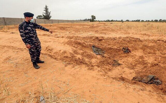 Un membre des forces de sécurité affilié au ministère de l'Intérieur du gouvernement libyen d'accord national (GNA) pointe le site signalé d'un charnier dans la ville de Tarhuna, à environ 65 kilomètres au sud-est de la capitale Tripoli, le 11 juin 2020. (Crédit : Mahmud TURKIA / AFP)