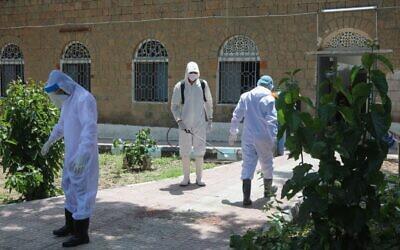 Du personnel médical yéménite désinfecte des combinaisons dans la cour d'un centre de quarantaine où des patients COVID-19 sont traités, dans la troisième ville du Yémen, Taez, le 21 juin 2020. (Crédit : AHMAD AL-BASHA / AFP)