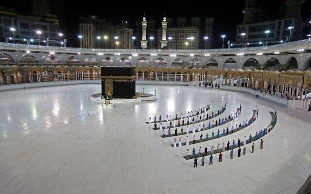 Cette photo prise le 23 juin 2020 montre quelques fidèles en train de réaliser la prière d'al-Fajr à la Kaaba, le sanctuaire le plus saint de l'Islam, au complexe de la Grande Mosquée du lieu saint de la Mecque en Arabie Saoudite. (Photo par STR / AFP)