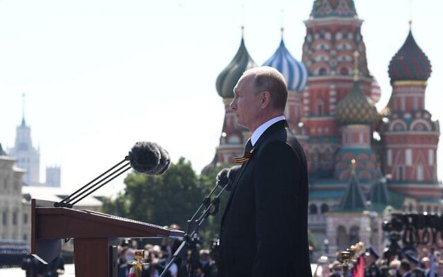 Le président russe Vladimir Poutine observe une minute de silence lors d'un défilé militaire marquant le 75e anniversaire de la victoire soviétique sur l'Allemagne nazie lors de la Seconde Guerre mondiale, sur la place Rouge à Moscou, le 24 juin 2020. (Crédit : Alexey NIKOLSKY / SPUTNIK / AFP)