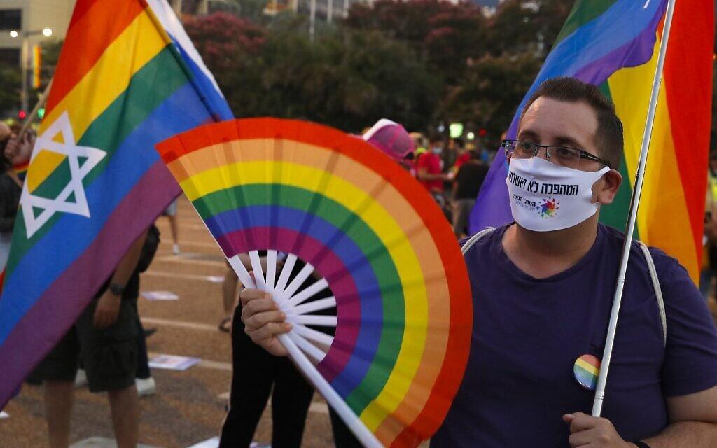 Des participants brandissent des drapeaux arc-en-ciel au défilé annuel de la fierté de Tel Aviv, le 28 juin 2020. (Crédit : JACK GUEZ / AFP)