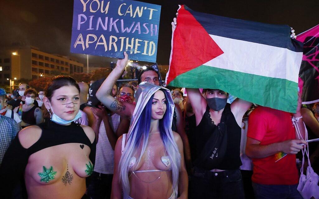 Des participants avec un drapeau palestinien et une pancarte dénonçant le «pink washing» en Israël, au défilé annuel de la fierté de Tel Aviv, le 28 juin 2020. (Crédit : JACK GUEZ / AFP)