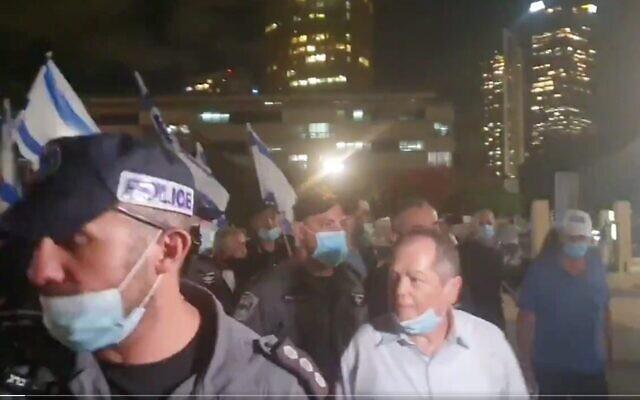 Capture d'écran d'une vidéo montrant le journaliste et commentateur Amnon Abramovich, au centre, escorté par la police après avoir été menacé par une foule lors d'une manifestation de droite à Tel Aviv, le 20 juin 2020. (Crédit : Twitter)