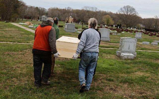 Le personnel du cimetière du Washington Memorial Park porte un cercueil pour l'inhumer, le 15 mai 2020. (Photo par Jonathan Alpeyrie/Polaris Images)