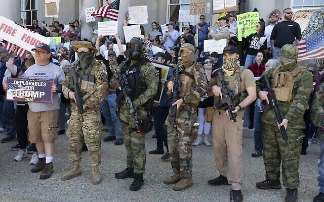 Des citoyens américains, y compris des membres du mouvement boogaloo, manifestent contre les fermetures d'entreprises en raison de la crise de coronavirus, à la State House à Concord, New Hampshire, le 2 mai 2020. (Crédit : AP / Michael Dwyer)