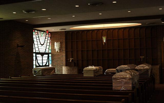 Les morts des suites de la COVID-19 attendent d'être enterrés. Les cercueils sont placés dans la chapelle principale de la maison funéraire Gutterman avant d'être transportés vers leur lieu d'inhumation final individuel dans un cimetière, le 15 mai 2020, à Woodbury, New York. (Photo par Jonathan Alpeyrie/Polaris Images)