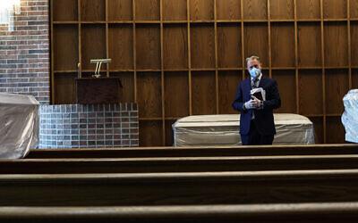 Le rabbin Greg Ackerman se tient à côté d'un défunt dans la chapelle du maison funéraire Gutterman, le 15 mai 2020, à Woodbury, New York. (Photo par Jonathan Alpeyrie/Polaris Images)