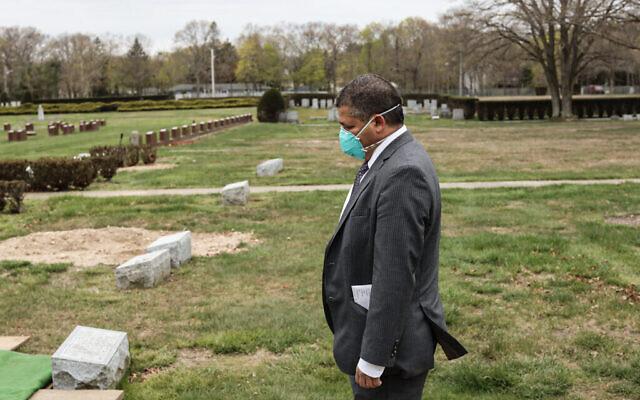 Stanley Parnes, chauffeur de corbillard à la maison funéraire Gutterman, assiste aux funérailles d'une victime du COVID-19 sans famille, par respect, le 15 mai 2020. (Photo par Jonathan Alpeyrie/Polaris Images)