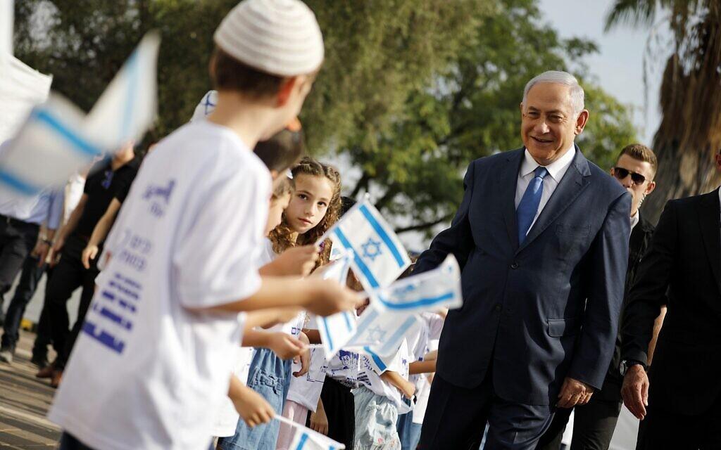 Le Premier ministre Benjamin Netanyahu, à droite, salue les élèves brandissant des drapeaux israéliens lors d'une cérémonie organisée lors de la rentrée scolaire dans l'implantation d'Elkana, en Cisjordanie, le 1er septembre 2019. (Crédit : Amir Cohen/Pool via AP)