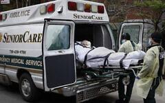 Un patient est emmené dans une ambulance par des urgentistes devant le centre de santé de Cobble Hill, dans le quartier de Brooklyn à New York, le 17 avril 2020. (AP Photo/John Minchillo, File)