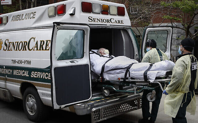 Un patient est emmené dans une ambulance par des urgentistes devant le centre de santé de Cobble Hill, dans le quartier de Brooklyn à New York, le 17 avril 2020. (AP Photo/John Minchillo, File)