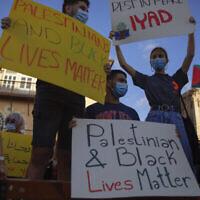 Des manifestants brandissent des pancartes pendant une manifestation à Jaffa contre la police israélienne après la mort d'un Palestinien autiste Iyad Halak, abattu par des policiers qui ont dit penser qu'il était armé, le 31 mai 2020 (Crédit :  AP Photo/Oded Balilty)