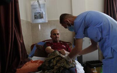 Un infirmier palestinien s'occupe de Jehad al-Qadra, atteint par un cancer, alors qu'il reçoit son traitement dans un hôpital du camp de réfugiés de Khan Younès, dans la bande de Gaza, le 16 juin 2020 (Crédit : AP Photo/Adel Hana)