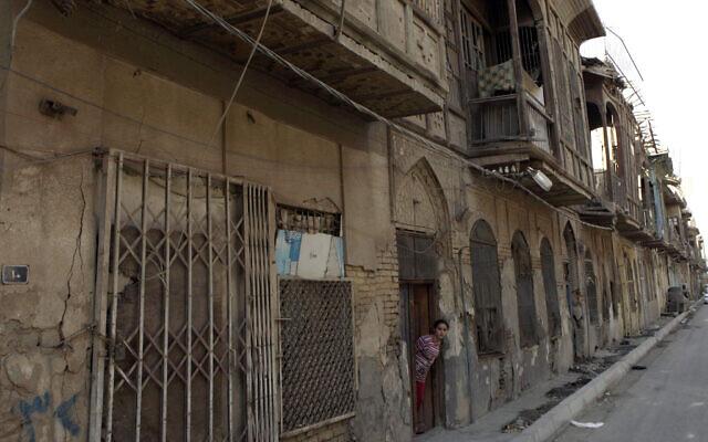 Une jeune Irakienne regarde par la porte de sa maison dans une rue de ce qui était autrefois le quartier juif du centre de Bagdad, en Irak, le lundi 26 septembre 2011. (AP/Karim Kadim)