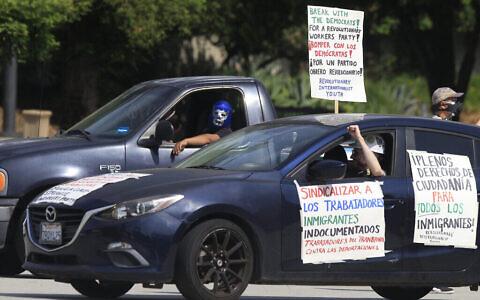 """Des travailleurs journaliers de Pasadena et leurs partisans organisent un """"rassemblement de voitures sûres COVID-19"""" pour protester contre l'exclusion des travailleurs de la protection financière dans le cadre de la pandémie actuelle pour les travailleurs immigrés essentiels devant l'hôtel de ville de Pasadena, en Californie, le mercredi 29 avril 2020. (AP Photo/Damian Dovarganes)"""