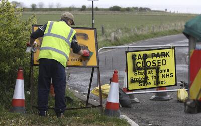 Un employé nettoie une croix gammée peinte à l'entrée d'une route et d'un parking fermé à Northumberland,  en Angleterre, le 30 avril 2020 (Crédit : Owen Humphreys/PA via AP)
