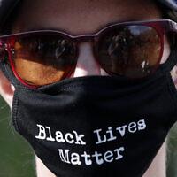 Un manifestant porte un masque facial lors d'une manifestation pour la mort de George Floyd, le dimanche 31 mai 2020, près de la Maison Blanche à Washington. Floyd est mort après avoir été immobilisé par des officiers de police de Minneapolis. (AP Photo/Alex Brandon)