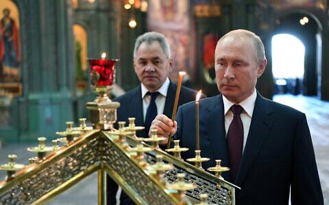Le président russe Vladimir Poutine, à droite, allume une bougie avec le ministre russe de la Défense Sergei Shoigu en arrière-plan, à la cathédrale des forces armées russes, le 22 juin 2020. (Crédit : Alexei Nikolsky, Spoutnik, Kremlin Pool Photo via AP)