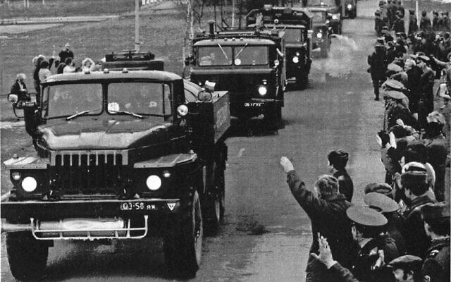 Des résidents applaudissent et saluent tandis qu'une colonne de véhicules armés transportant d'anciennes troupes soviétiques quitte Vilnius, le 3 mars 1992. (Crédit : Mendaugus Kublis / AP)