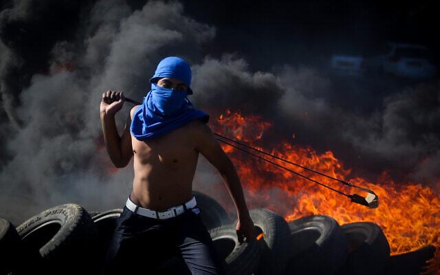 Photo d'illustration : Des manifestants palestiniens utilisent des frondes pour jeter des pierres aux soldats israéliens au cours d'affrontements à proximité de l'implantation de Beit El, le 13 novembre 2015 (Crédit : FLASH90)