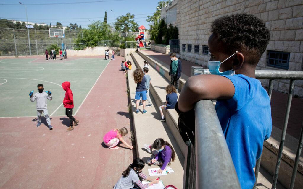 Des élèves israéliens à leur retour à l'école pour la première fois depuis le début de l'épidémie, début mai, portant des masques, respectant les règles de distanciation sociale et montrant des notes médicales signées (Autorisation : Olivier Fitoussi/Flash90)
