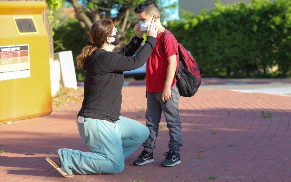 Des enfants israéliens portent le masque pour aller à l'école du  Moshav Yashresh,  le 3 mai 2020 (Crédit : Yossi Aloni/Flash90)