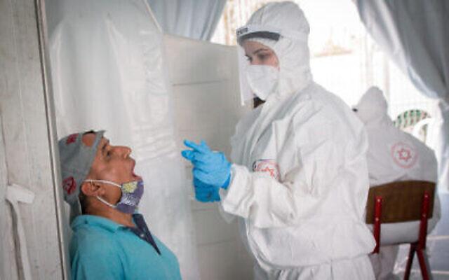 Les personnels médicaux du Magen David Adom réaliser des prélèvements pour dépister le nouveau coronavirus, dans le sud de Tel Aviv, le 2 juin 2020 (Crédit : Miriam Alster/Flash90)
