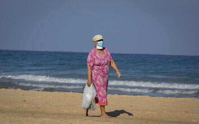 Une femme israélienne portant un masque marche sur la plage de la ville côtière d'Ashdod, dans le sud du pays, le 12 juin 2020 (Crédit : Olivier Fitoussi/Flash90)