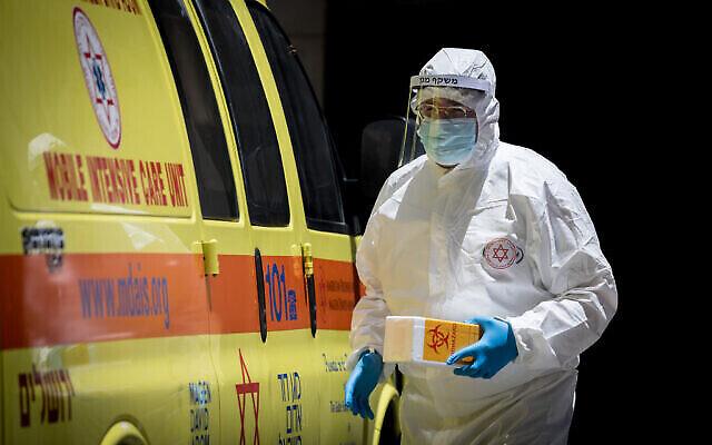 Un employé du Magen David Adom s'apprête à tester un patient présentant des symptômes de coronavirus à Jérusalem, le 23 juin 2020. (Crédit : Yonatan Sindel / Flash90)