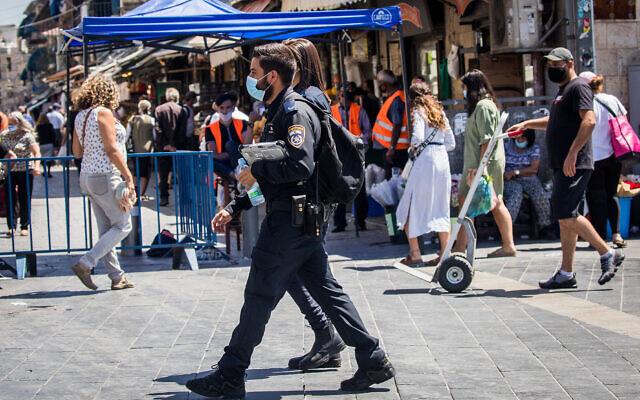 Des agents de police font appliquer les directives de distanciation physique au marché Mahane Yehuda, à Jérusalem, le 25 juin 2020 (Crédit : Yonatan Sindel/Flash90)