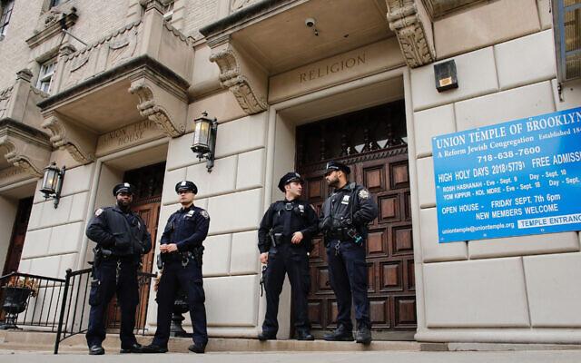 Des agents de la police de New York montent la garde à l'entrée de l'Union Temple de Brooklyn après sa profanation par des graffitis, le 2 novembre 2018 (Crédit :  Kena Betancur/AFP via Getty Images)