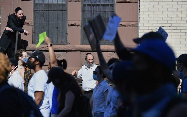 """Des membres de la communauté juive orthodoxe regardent les manifestants traverser le quartier de Brooklyn le 3 juin 2020, lors d'une manifestation """"Breonna Taylor and Black Lives Matter"""" à New York, après la mort récente de George Floyd, immobilisé par la police de Minneapolis. (Photo par Angela Weiss / AFP via Getty Images/ via JTA)"""