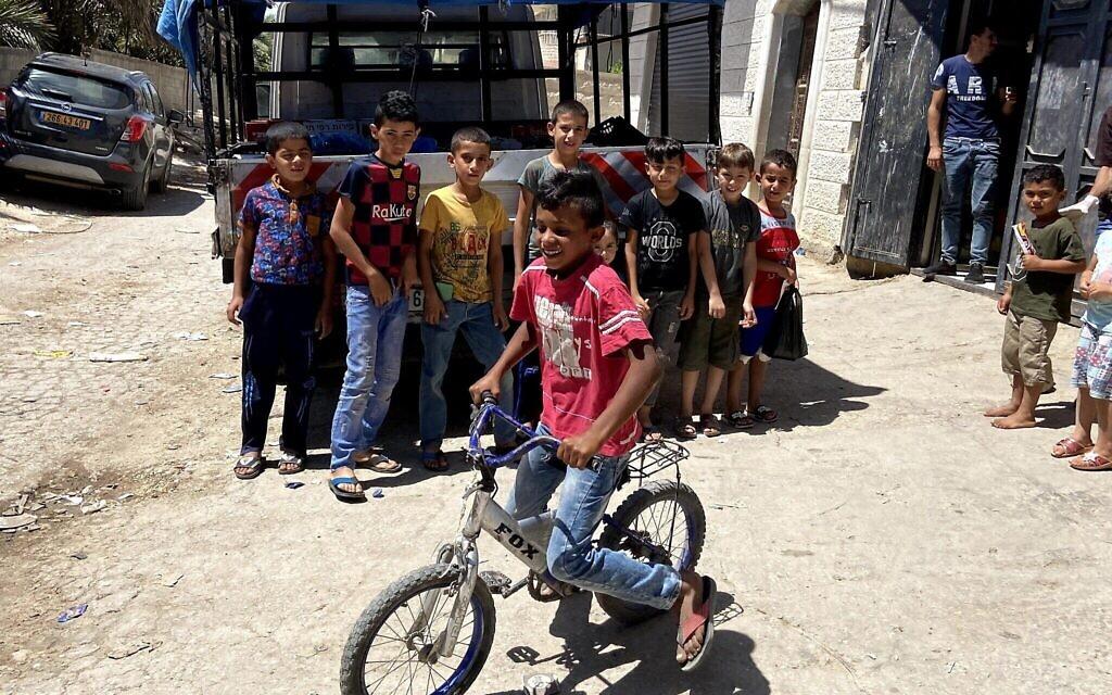 Des enfants posent pour une photo dans le village palestinien de Fasa'il, dans la vallée du Jourdain, le 10 juin 2020. (Jacob Magid / Times of Israel)