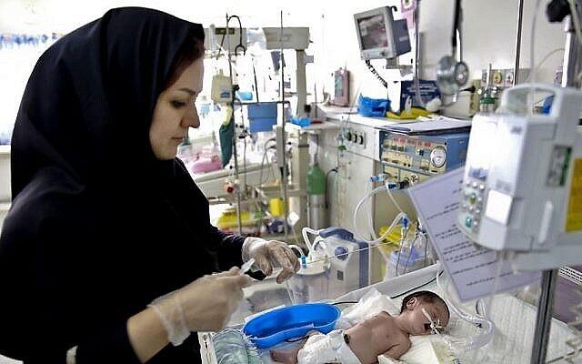 Une infirmière au chevet d'un nouveau-né à l'unité de soins intensifs de néonatologie à l'hôpital pour enfants Mofid à Téhéran, le 30 décembre 2013. (Crédit: AP/Ebrahim Noroozi)