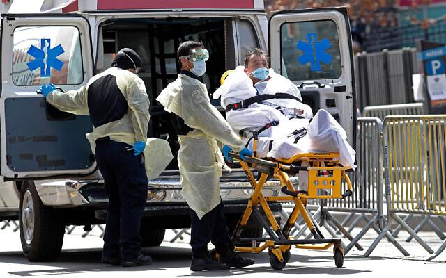 Un patient est transporté du centre hospitalier d'Elmhurst vers une ambulance en attente, dans le quartier du Queens à New York, le 7 avril 2020. (AP/Kathy Willens)