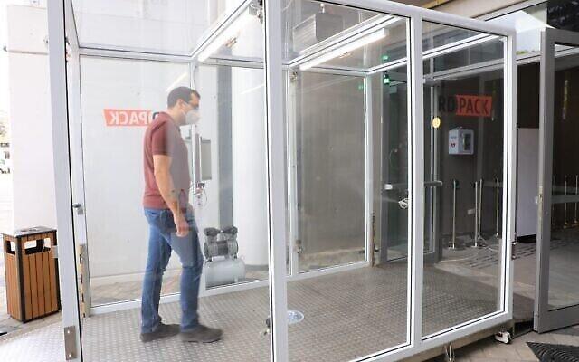 Le Dr Izaak Cohen, chercheur à l'université Bar-Ilan, traverse le tunnel d'assainissement et de désinfection développé par RD Pack, stade Bloomfield, Tel Aviv, 2 juin 2020 (Crédit : Yoni Reif)