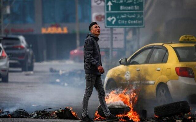Un Palestinien marche à côté de pneus en feu au cours d'affrontements avec les forces israéliennes à l'entrée nord de la ville cisjordanienne de Ramallah, le 14 février 2020. (ABBAS MOMANI/AFP)