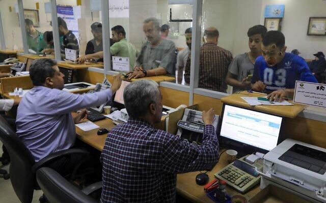 Des Palestiniens reçoivent 100 dollars d'aide financière pour les familles dans le besoin. L'aide est offerte par le Qatar et versée dans un bureau de poste à Gaza Ville le 27 juin 2020. (Photo par MAHMUD HAMS / AFP)