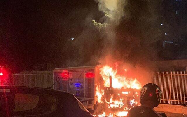 Des pompiers israéliens s'activent pour éteindre un véhicule en feu à Jaffa, le 13 juin 2020, alors que les manifestations se poursuivent contre un projet de la ville de construire un abri pour SDF sur un ancien cimetière musulman. (Pompiers israéliens, Dan District)