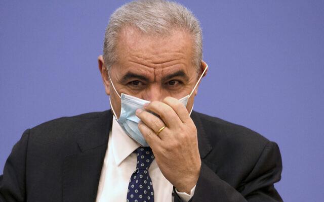 Le Premier ministre palestinien Mohammad Shtayyeh retire son masque de protection lors d'une conférence de presse à la Foreign Press Association dans la ville cisjordanienne de Ramallah, le mardi 9 juin 2020. (Abbas Momani/Pool Photo via AP)