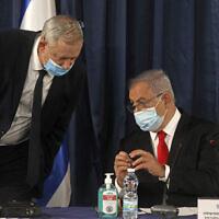 Le Premier ministre israélien Benjamin Netanyahu (à droite) parle au ministre de la Défense Benny Gantz, alors que les deux hommes portent un masque de protection en raison de la Covid-19 lors du conseil des ministres hebdomadaire à Jérusalem, le dimanche 7 juin 2020. (Menahem Kahana/Pool Photo via AP)
