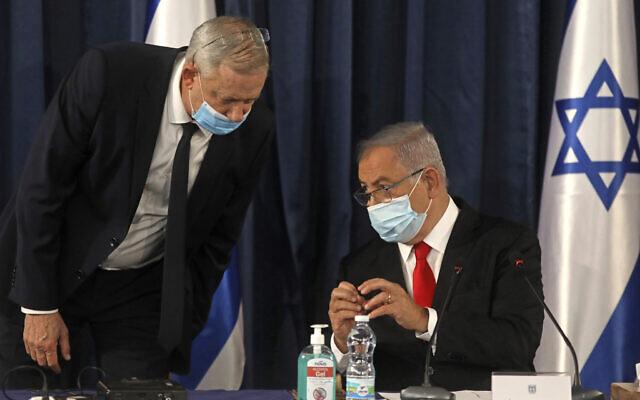Le Premier ministre israélien Benjamin Netanyahu parle au ministre de la Défense Benny Gantz, alors que les deux hommes portent un masque de protection en raison de la Covid-19 lors du conseil des ministres hebdomadaire à Jérusalem, le dimanche 7 juin 2020. (Menahem Kahana/Pool Photo via AP)