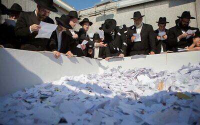 Des hommes prient devant la tombe du défunt rebbe loubavitch Menachem Mendel Schneerson pour le 20ème anniversaire de sa mort au Queens, Ney York, le 1 juillet 2014. (Adam Ben Cohen/Chabad.org)